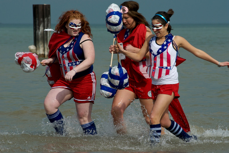 Three women dressed in American Gladiator costumes running out of the water. The Polar Plunge is an annual fundraising event in Chicagoland, raising funds for Special Olympics and Special Children's Charities. Participants often dress in costumes as they leap in to the frigid 34 degree waters of Lake Michigan. Similar events are held around the country, benefiting Special Olympics.