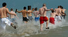 A group of shirtless men leap in to the freezing waters. The Polar Plunge is an annual fundraising event in Chicagoland, raising funds for Special Olympics and Special Children's Charities. Participants often dress in costumes as they leap in to the frigid 34 degree waters of Lake Michigan. Similar events are held around the country, benefiting Special Olympics.