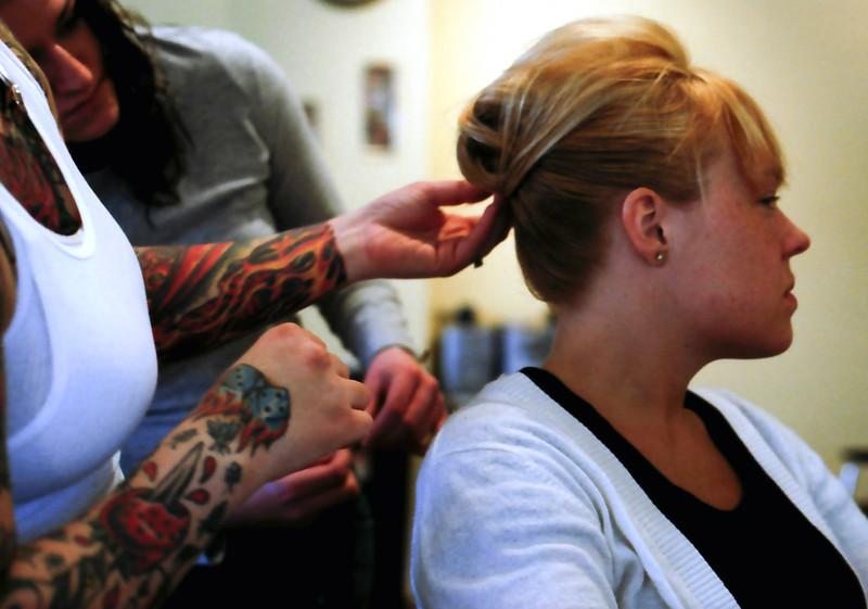 Beautician with tattoos creating hairdo on customer. Twisted Scissors beauty salon in Chicago, Illinois, Logan Square neighborhood. January 2007.