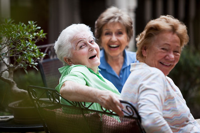 Three elderly women laughing on patio