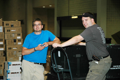 "Carter Smithhart and Rob Rydberg set up one of many Internet Cafes located throughout ""El Puente,"" the Interaction Center located in the Henry B. Gonzalez Convention Center."