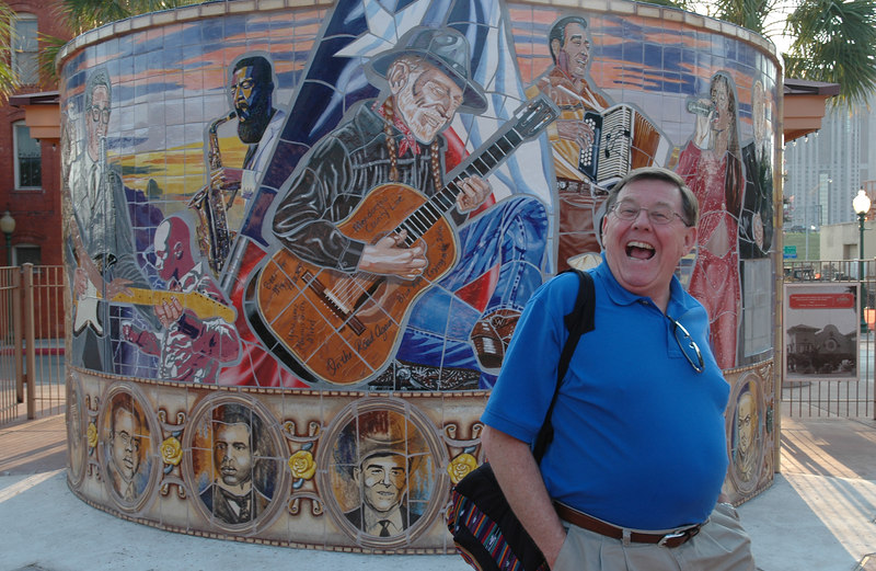 Bill Kees, Director, poses by a mural of Texas legends in the Sunset Station near the Alamodome.