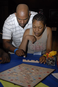 Jason Bennett lends Latoya Brown a hand in a game of Scrabble at the Multicultural Youth Leadership Event, part of the 2006 ELCA Youth Gathering.