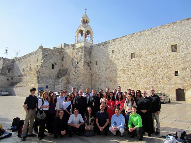 Pilgrims pose for a group photo outside the Church of the Nativity of Christ.