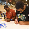 WELCA @ 2018 ELCA Youth Gathering | Thomas Hawkins (left) and his son, Nicholas Hawkins, Christ the King Lutheran, Universal City, Tx., write messages on compassion cards that will be placed in the bags for the recipient.