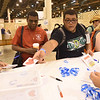 WELCA @ 2018 ELCA Youth Gathering | Thomas Hawkins (left) and his son, Nicholas Hawkins, Christ the King Lutheran, Universal City, Tx., leave messages on compassion cards that will be placed in the bags for the recipient.