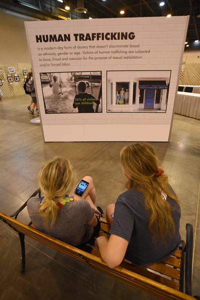 WELCA @ 2018 ELCA Youth Gathering | Macy Schendel And Autumn Lawless, Grace Lutheran, Ripon, Wisc., sit on the bench near the human trafficking installation.