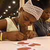 "WELCA @ 2018 ELCA Youth Gathering | Zawadi Balomona, Umoja, Fort Worth, Tx.,  writes a message of comfort on a ""compassion card."""
