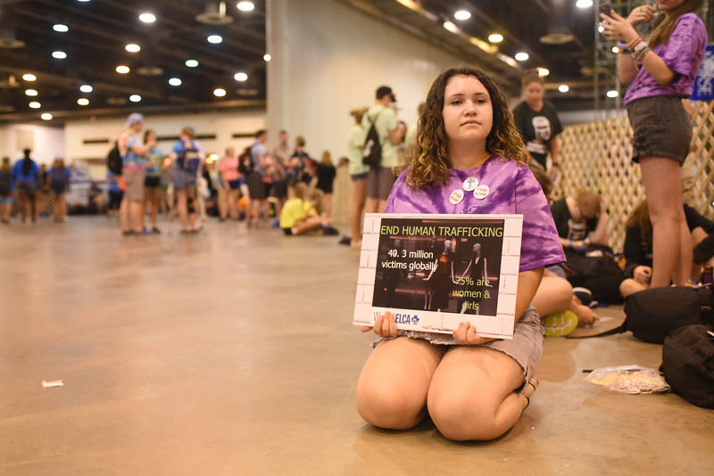 "WELCA @ 2018 ELCA Youth Gathering | Ashley Haas, St. Michael's Lutheran, Wellington, Fla., holds a sign with the statistic: ""40.3 million victims globally."""