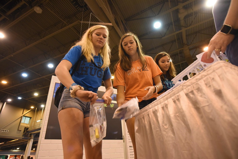 WELCA @ 2018 ELCA Youth Gathering |  Julia Kasper, Kelly Kettler and Cori Kettler, First English Lutheran, Platterville, Wisc., add lotion and body wash to their hygiene bags.