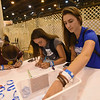 WELCA @ 2018 ELCA Youth Gathering | Sarah Baker (right), Elise Poe-Johnson, and Callie Wright, write messages of hope at the compassion station.