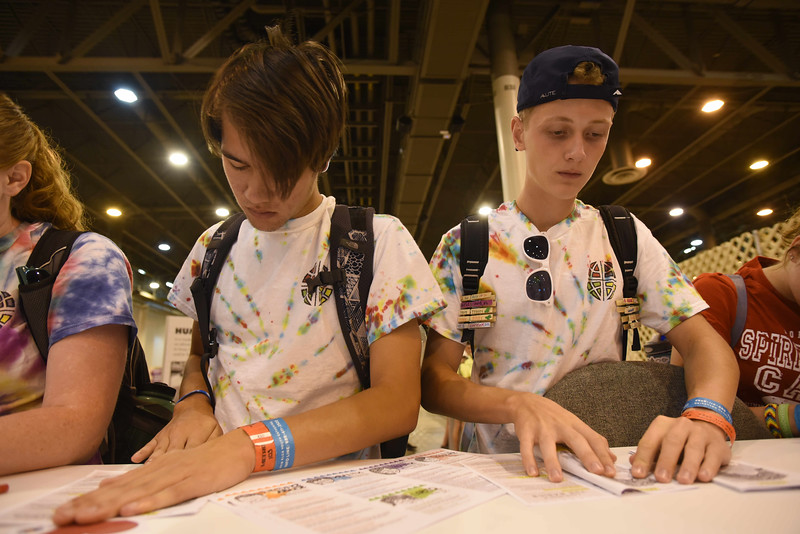 WELCA @ 2018 ELCA Youth Gathering | Matthew Minoymany and Alex Murphy, Trinity Lutheran Church, Newport News, Va., fold pamphlets to place in each bag.