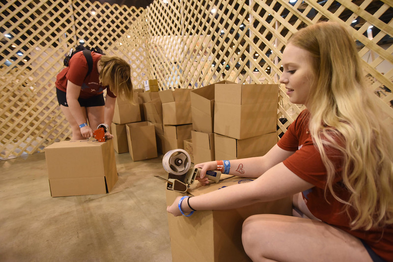 WELCA @ 2018 ELCA Youth Gathering | Karlee Fick, First Lutheran, Lake City, Minn., and Maddie Gates tape up boxes that contain finished hygiene kits. These boxes will be given to United Against Human Trafficking, Houston.