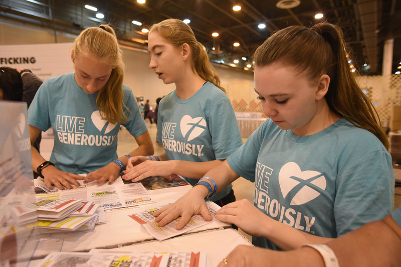 WELCA @ 2018 ELCA Youth Gathering | Alli Fogelberg, Clair Fogelberg, and Megan Reigel, West Immanual Lutheran Church, Osceola, Wisc., fold a pamphlet of resources that will be added to each bag.