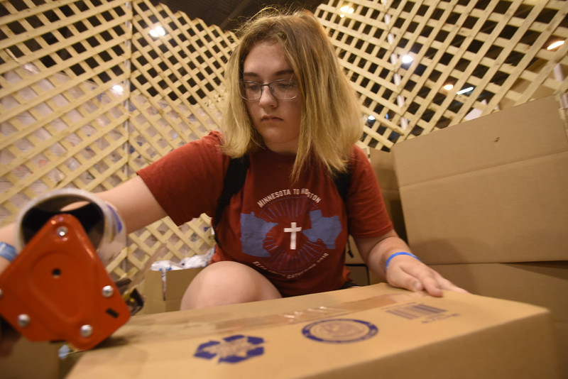WELCA @ 2018 ELCA Youth Gathering |  Maddie Gates, First Lutheran, Lake City, Minn., tapes up boxes of hygiene items  to be given to United Against Human Trafficking for their street outreach program.