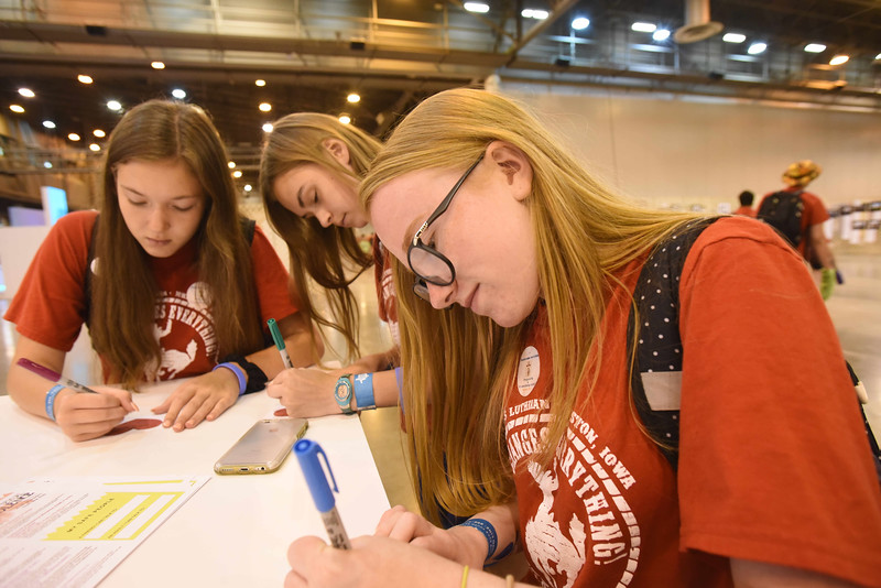 "WELCA @ 2018 ELCA Youth Gathering | Nikki Luebke (left), Jaycie Aanonson and Morgan Dunn, St. James, Johnston, Ia.,write messages for the recipients receiving bags at the ""Compassion Station."""
