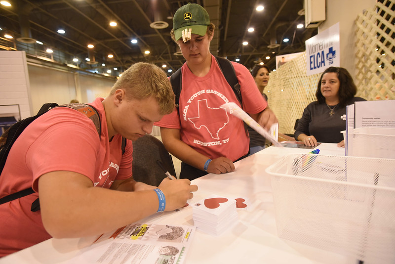 WELCA @ 2018 ELCA Youth Gathering   Damien Waller and Jared Bartos, Boyceville, Wisc., Trinity Lutheran, fold a pamphlet with resources that are available to those receiving the hygiene bags.