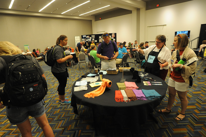 "Women of the ELCA @ ELCA Youth Gathering | Detroit, Michigan, July 15-19 2015 | Linda Post Bushkofsky points out Women of the ELCA items for sale at the ""shop"" in the adult leaders cafe."