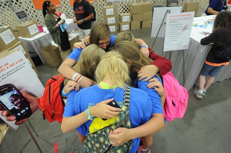 Women of the ELCA @ ELCA Youth Gathering | Detroit, Michigan, July 15-19 2015 | Danielle Miller, Lizzy Hellsten, Maddie Franklin, Claire Fitzpatrick, Christ The Lord, Lawrenceville, Ga., pray before writing assembling in-kind gifts.