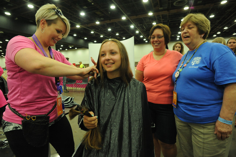 Women of the ELCA @ ELCA Youth Gathering | Detroit, Michigan, July 15-19 2015 | Candie Yon, Children Without Hair, cuts Sarah Guy's hair while her mom, The Rev. Juli Lejman-Guy and grandmother, Carolyn Steinfeldt, Zion Lutheran, Sandusky, Oh., watch as more hair is cut.