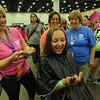 Women of the ELCA @ ELCA Youth Gathering | Detroit, Michigan, July 15-19 2015 | Candie Yon, Children Without Hair, cuts Sarah Guy's hair while her mom, The Rev. Juli Lejman-Guy and grandmother, Carolyn Steinfeldt, Zion Lutheran, Sandusky, Oh., watch as Sarah holds many inches of her former hair in her hand.
