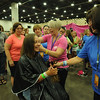 Women of the ELCA @ ELCA Youth Gathering | Detroit, Michigan, July 15-19 2015 | WELCA woman, Sarah Guy, St. John's Lutheran, Bellevue, Oh., hands off her hair to another WELCA woman, Carolyn Steinfeldt, Zion Lutheran, Sandusky, Oh., who is volunteering in the Children With Hairloss exhibit in the Community Life area.