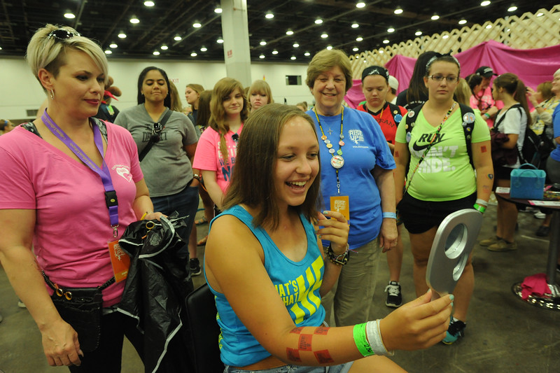 Women of the ELCA @ ELCA Youth Gathering | Detroit, Michigan, July 15-19 2015 |  WELCA woman, Sarah Guy, St. John's Lutheran, Bellevue, Oh., checks out her new look after donating several inches of hair to Children With Hairloss.