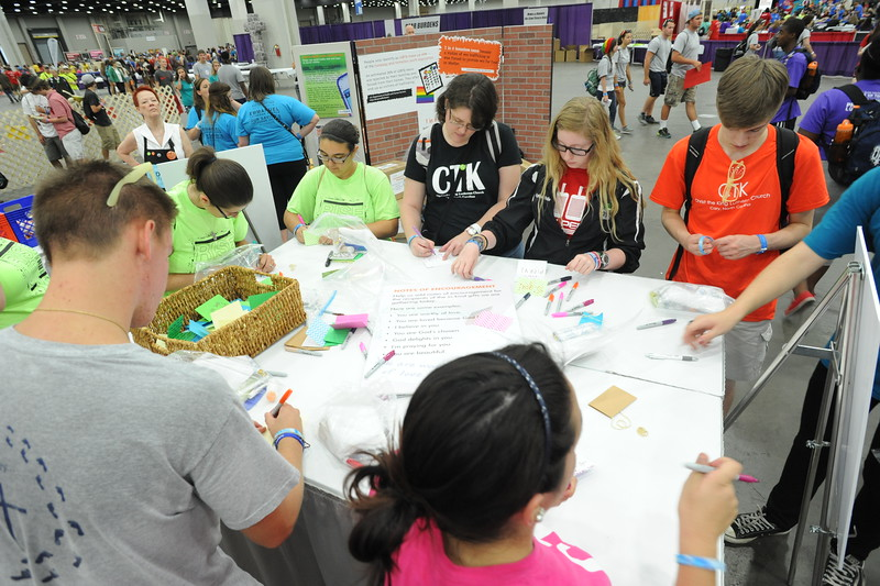 Women of the ELCA @ ELCA Youth Gathering | Detroit, Michigan, July 15-19 2015 | Youth gathering attendees write notes at the encouragement station in the WELCA exhibit.