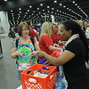 Women of the ELCA @ ELCA Youth Gathering | Detroit, Michigan, July 15-19 2015 | Assembling hygiene kits. Valora Starr, right, instructs visitors to the exhibit about placing a toothbrush, toothpaste, deodorant, soap, lip balm, shampoo, conditioner, tampons, lotion and a towel in every bag.