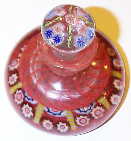 """DCP04925YVP Inkwell... Ysart/Vasart YVP period inkwell with a 9 spoke millefiori base in a 1-2 design cartwheel set on a translucent red ground with a red ribbon swirl top, 4.0"""" wide at base x 2.9"""" tall without the stopper x 3.95"""" tall with the stopper and 24.0 ozs. It's obvious that the stopper is not the correct one for this inkwell. Base is concave and fire-polished with a raised and uncut (sharp edges) pontil mark. No label. circa 1946 to 1956/59. acquired 06-29-10."""