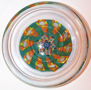 """DCP04694YVP Pindish... Ysart/Vasart YVP pindish with 10 spokes in a 1-1 design cartwheel set on a dark green ground, 4.7"""" x 1.1"""" and 18.0 ozs. The latticino spoke strands are very, very fine as to almost be invisable, This is a very interesting paperweight pindish. In my opinion it definitely has Ysart/Vasart canes in it circa 1946 to 1955 but I indicate it as circa 1946 to 1956/59...why?...because it has the remains of a Vasart Label on the base. It was in 1956 with the association of George Dunlop of Pirelli Glass that Pirelli began to use the Black and Silver Pirelli label and that Vasart began to use the Black and Silver Vasart Label so I think that this Pindish is a TRUE transitional piece...made in the period of 1946 to 1956/59 and sold as a Vasart with a Vasart label. Note also that it has the same outer cane as the preceeding pindish #4343 and the outer cane in my YVP7 large spoke weight #4358. The base is polished flat with a rough ground out pontil mark area. Remains of a Black Vasart label on the base. circa 1946 to 1955/59, acquired 01-18-06."""