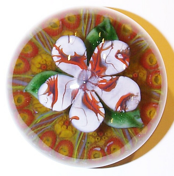 "DCP04923YVP Flower... Ysart/Vasart flower weight with a five petal flower over three green leaves set on an 8 spoke millefiori 1-2 design cartwheel and a yellow ground, 3.45"" x 2.85"" and 27.0 ozs. Concave fire-polished base with a deep concave rough ground pontil mark area. No label. circa 1946 to 1956/59 and possibly to 1964. acquired 05-17-10."