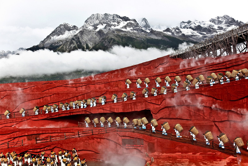 """Impressions of Lijiang,"" with the Jade Dragon Mountain at 3.200m looming behind the outdoor theater.  It is truly a spectacle of local culture, with five hundred of the Naxi ethnic group people performing songs and dances - It is the highest altitude production ever staged, directed by Zhang Yimou,"