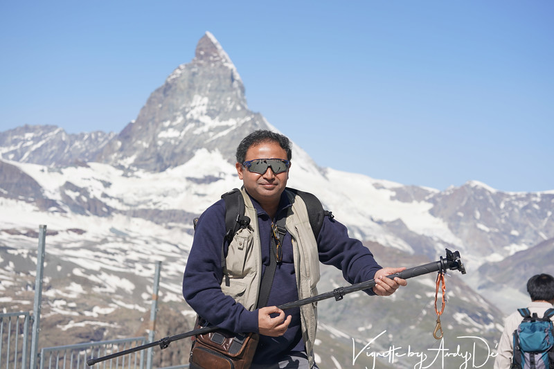 "The Shutterbug-Blogger-DJ-Explorer, <br /> an aspiring Musician with wind swept hair, <br /> merrily strumming his 'Air-Guitar',<br /> inspired by the iconic Matterhorn as the Swiss Alpine backdrop spectacular, <br /> so painstakingly crafted by Mother Nature!<br /> <br /> Howzat for a ""Poetic"" caption?!"