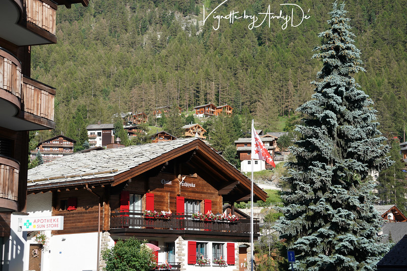 Main Street Zermatt with a Swiss Chalet styled Hotel with houses on the slopes of the mountain range, making for a picturesque backdrop!