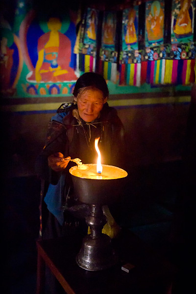 Tending the butter lamp, Stongdey Monastery.