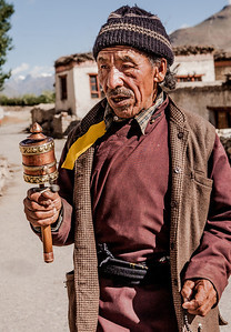 A man dressed in traditional Zanskar outfit walks down the street with the Mani prayer wheel in one hand and a string of beads in the other in the sani village in Zanskar, a remote and isolated valley in India.