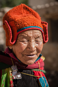 Portrait of an old woman, face covered in wrinkles wearing a bright orange woolen cap, typical of the Zanskar region, a remote and isolated valley in India.