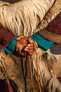 An old Zanskari woman, wearing a goatskin coat, chanting with the help of prayer beads, walking down the streets of Sani village in the remote and isolated offbeat Zanskar valley.