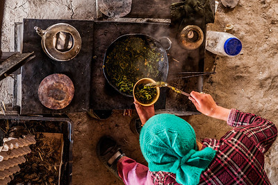 Top view of the wood fired stove and a wok with a steaming hot preparation of fresh locally gown green veggies being served by the daughter of the family of our homestay in Sani, a village in the remote and isolated Zanskar valley.