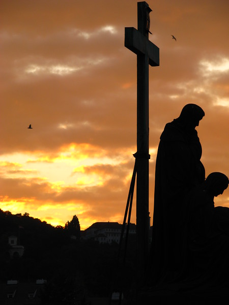Cross and statue at sunset