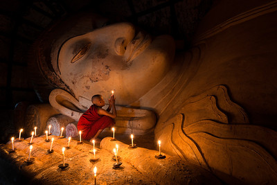 A monk offers a candlelit prayer to reclining Buddha  Bagan, Myanmar