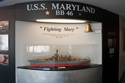 This displays honors the USS Maryland, a Colorado-Class Battleship, commissioned in 1921.  One of the survivors of the attack at Pearl Harbor, she went on to earn 7 battle stars during the war, participating in many of the major actions in the Pacific Theater including Midway, Tarawra, Saipan, Leyte Gulf, and Okinawa.  A monument to the battleship, incorporating the ships bell, stands on the grounds of the Maryland State House.