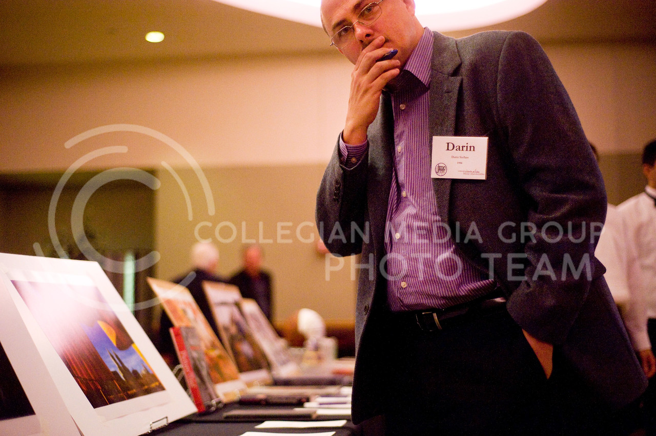 Darien Siefkes, an A.Q. Miller School of Journalism and Mass Communications alumnus, bids on photographs at the JMC Centennial event Friday night.