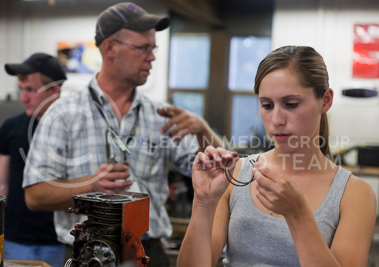 Nicole Allen, senior in animal science, examines piston rings from a lawn mower engine as her instructor Bob Whearty demonstrates how to clean pistons in the ag power class at Manhattan Area Technical College Tuesday evening. The class is made up of MATC students as well as K-State students.