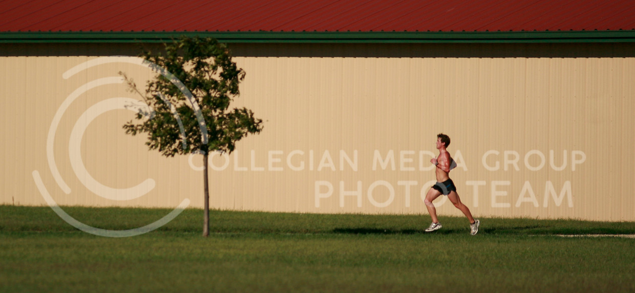 A member of the men's cross country team runs alongside a building during practice Saturday September 11.
