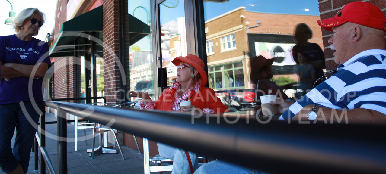 Eleonore Ingram, a Topeka resident and K-State alumna, leans against the new railing at Radina's Coffee House and Roastery in Aggieville to talk With Colleen O'Brien, of Jefferson, Iowa, and Paddy O'Hyland, of Woodland Park, Colo. The patio area at the Aggieville Radina's location was completed last week.