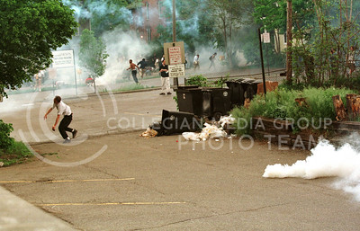 An Anti-Klan protester throws rocks at police during a Ku Klux Klan rally in Ann Arbor, Michigan on Saturday, May 9, 1998.  Hundreds of protesters confronted the Klan, who were protected behind a chainlink fence at the Ann Arbor City Hall, and police used tear gas to disperse the crowds during the  noon rally.  Several people were hurt, but no arrests were made.
