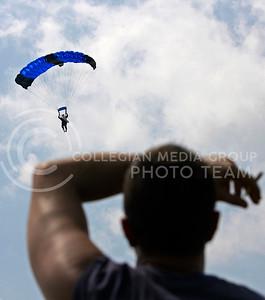 "Jason ""Captain Morgan"" Purintan, Kansas State University Parachute Club member, guides a skydiver in to a safe landing on July 26, 2008 at the Wamego airstrip. Many people jumped for the first time that Saturday after taking one of the KSUPC's parachuting clases which are only held six times a year."