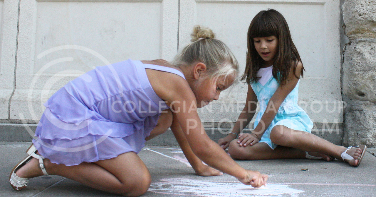 Madison Tiberio, Manhattan resident, and her friend Avery Shipper, Junction City resident, color with chalk on the sidewalk outside The Chef on Sunday afternoon.